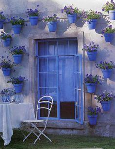 des pot à fleurs bleus accrochés au mur avec des fleurs bleues