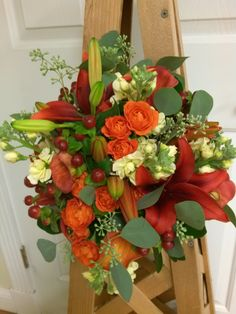 Fall Hand Tied Bridal Bouquet of Pale Yellow Stock, Red Asiatic Lilies, Mango Calla Lilies, Orange Spray Roses, Red Hypericum Berries and Seeded Eucalyptus.  Designed by Colonial Florist, Gordonsville, VA.