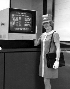 (07Nov68) United Air Lines hostess displays new television flight board monitors at Midway.
