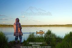 Photo of Elder native Yupik woman stands on shoreline of Kuskokwim River looking to distant WE Alaska Summer