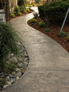 I like the impressed concrete curved walkway and the garden treatment. It really pulls the eye along.