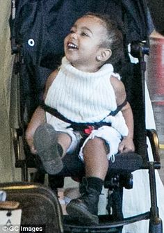 Giddy: The onlyonly child of Kim Kardashian and Kanye West giggled as she sat in her pram...