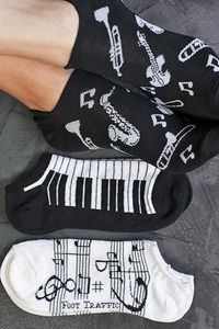 Music notes, instruments and piano keys all together for a symphony of fun in a footie that will hide in your shoes while you play all day, or night..