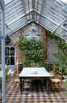 A conservatory extension has a tiled floor and a large marble topped table