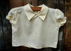 1950S CREAM BLOUSE  10.00 1950's Cream blouse with pointed collar and puff sleeves approx. age 6-12 months  Cotton blouse with pointed collar. Button fastening at the rear. Light and cool for summer, and in great condition.  Circa: Early 1950's, possibly late 1940's.  Good condition