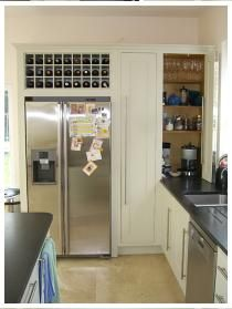 Housing for American fridge freezer with integral wine rack, tea and coffee cupboard with bifold door shown open.