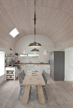 Wood, white & metal kitchen. Love the wooden arched ceiling, rough cut wood table and metal chairs