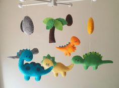 ((( INCLUDES ))) This nursery mobile contains five dinosaurs, one palm tree and four dinos eggs. They are suspended from a wood hanger, about 13 x 13. This item made by hand - no machines involved. I hand-cut, hand-sewn each item with quality wool felt and hypo-allergenic cluster fiber. The wood hangers are also handcrafted. And it is possible to make it so the animals appear to be looking down. Please leave a note when you check out for it. Making each mobile with lots of love and care…