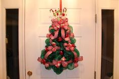Get your Christmas tree ready for Santa. This whimsical tree is a great accent for your door or to hang anywhere in your home. It's quick and easy. I'll show you how.Here is a list of materials needed:Christmas tree shaped work wreath1 green roll of deco poly mesh with foil1 roll of ribbon8 Christmas ornaments2 Christmas picksFloral wireScissors and wire cuttersHot glue gunLet's begin.Staring at the top point, attach the mesh all the way around the outer wire of the tree form.Once you m...
