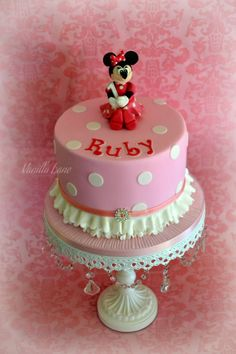 Minnie Mouse themed 1st Birthday Cake.   Cake was quite a tall 4 layered 8 caramel mud filled with caramel buttercream and covered with white chocolate ganache and then fondant.  Minnie was make from modelling paste.