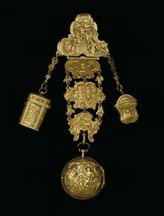 Equipage (Chatelaine) ca. 1730-1750, Gold. A long hook at the back to hang from the belt. London hallmarks on the hook precisely to 1755-6. There are 3 objects suspended from the chatelaine. Middle: A watch, which bears the name of the watchmaker, Robert Cawley, Chester, movement no. 91. The watch and the small empty container or étui on the right are of approximately the same date as the chatelaine. The étui for snuff, ca.1730 contains a small gold spoon for ladling out the snuff.