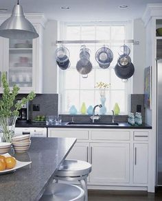 Keep pots and pans convenient with a hanging pot rack. Here a stainless-steel rack -- just above the sink -- allows the homeowner to wash pots and pans and hang them up to dry in the same spot. White Kitchen Sink, New Kitchen, Kitchen Decor, Kitchen Small, Kitchen Ideas, White Cupboards, Kitchen Modern, Kitchen Island, Kitchen Cabinets