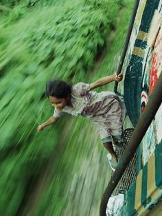 A Bangladeshi girl hangs on to the side of a train, Unknown Source