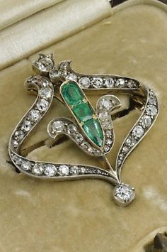 An antique gold, diamond and emerald brooch, makers mark: *T, retailed by Samuel Arndt, St Petersburg, circa 1880. Of openwork elliptical design, centring on three emeralds and set throughout with circular- and rose-cut diamonds, suspending an articulated diamond-set drop, held in original fitted case, height: 3.5cm.