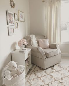 Neutral white, gold, and blush pink nursery. Beige rocker. Glider. Baby girl. Rocking chair. Pink flowers. Hydrangeas. Framed art. Wall gallery. White nightstand. Gold drawer pulls. Gold basket. White basket. Stuffed animals. Trefoil rug. White curtains. Gold curtain rod. Corner chair.