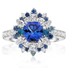 These natural gemstones have been selected by hand to create this designer piece. Featuring a square cushion shaped tanzanite at its centre which is then accented by blue sapphires, bright blue apatite and sparkling round, marquise cut and princess cut diamonds. By Gerard McCabe