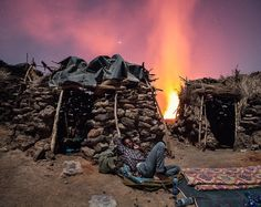 photo by @andrea_frazzetta // Volcano Erta Ale, Ethiopia. A small settlement consisting of a few stone huts is the only outpost to the crater rim where you can spend the night. In this image there is Binyam, my local guide, sleeping on the doorway of my stone hut.  I will remember forever this night. The vibrant ground at the edges of the volcano and the sound of the lava as a background. They brought me some of the most intense dreams I've ever done. @andrea_frazzetta #Danakil #Ethiopia…