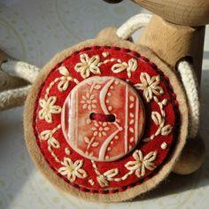 Brooch made of felt, with a clay knob and embroidered bavlnkama. Equipped with safety pin. It is slightly curved, padded hollow fiber. Size 6.5 cm. keramickým knoflíkem, moje práce