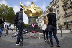 "People stand in front of the ""Flame of Liberty"" statue in memory of Britain's Princess Diana near the Pont de l'Alma in Paris August 31, 2012. People left flowers and messages near the statue to mark the 15th anniversary of the death of Princess Diana. REUTERS/Gonzalo Fuentes (FRANCE - Tags: ANNIVERSARY ROYALS SOCIETY)"