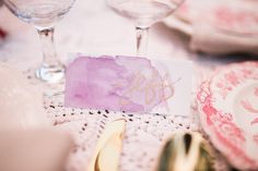purple watercolor and gold calligraphy escort cards
