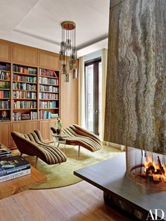 The library of designer Laura Santos's New York townhouse features chaise longues covered in a Designers Guild fabric. The vintage FontanaArte light fixture is from Bernd Goeckler Antiques, and the rug is by BDDW | archdigest.com