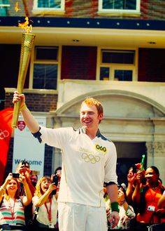 Rupert Grint holds the Olympic Flame at Middlesex University in London (July 25, 2012)