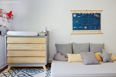 Cômoda de madeira e laca com desenho retrô e cama baixinha com almofadas em tons de cinza.