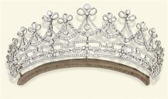 A BELLE EPOQUE DIAMOND TIARA  Designed as a series of graduated old-cut diamond garlands each surmounted by a ribbon bow and diamond collet suspending articulated knife-edge bar and circular-cut diamond drops, above a stylised geometric foliate frieze, mounted in platinum and gold, circa 1905, 23.5 cm inner circumference, in original fitted blue leather case, Christie's, London, 10 Dec., 2008, formerly property of Lady Emilie Harmsworth.
