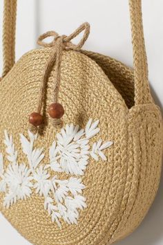 Round, braided shoulder bag with an embroidered motif. Tie closure with wooden beads at ends. Width 2 in. Round Straw Bag, Round Bag, Crochet Handbags, Crochet Purses, Crochet Shoulder Bags, Diy Sac, Diy Handbag, Jute Bags, Basket Bag