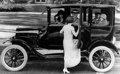 Early 1920s. Love the woman's hat (on the left), love the beautiful sweep of the lady's skirt as she climbs into the car.