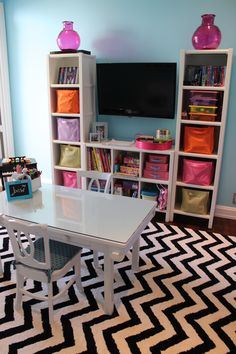 My Daughter's Contemporary Playroom.  Great storage unit with bins helps organize toys and keep the room tidy.  TIP: GET A PIECE OF GLASS CUT TO TOP YOUR PLAYTABLE, AND YOU'LL AVOID IT BEING RUINED DURING ART TIME! THIS TABLE IS 3 YEARS OLD, BUT STILL LOOKS NEW!    tags: turquoise, black and white, chevron rug, land of nod, bright, fun, girl's, toddler, children, play, playroom storage, entertainment center, TV, cubbies.