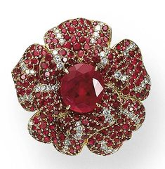 """A SPECTACULAR RUBY AND DIAMOND """"CAMELLIA"""" RING, BY CHANEL  The ring, centering upon an oval-shaped ruby pistil, extending overlapping pavé-set ruby petals, accented by circular-cut diamond veining, the hoop designed as a stylized branching stem, mounted in 18K gold"""