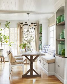 Subtle pops of green and blue, like the indigo print breakfast nook pillows, keep the dining room in this rural Connecticut farmhouse bright. The homeowner displays her collection of blue and green demijohn bottles on either side of the dining room table in built in shelves.