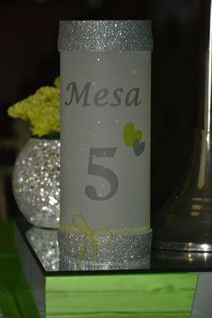 Marcador de mesa tubular com vela no interior em prata e verde.