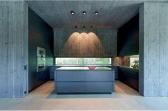 Küche mit Kücheninsel, Wänden in Betonoptik, gezielter Beleuchtung und einem langen, schmalen Fenster von Josko. Josko | www.josko.at
