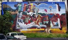 The mural was painted by Keith Hollander at Market St. and Duboce Ave, in San Francisco.   Titled Joyous Discoveries: A Journey Through Books and Music, this mural, by Keith Hollander won the Public Mural Award of 2001 for the Finest Mural in the SF Bay Area.   The mural is now being lost due to construction on this corner.