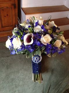 Blue delphinium, white roses, Picasso calla lilies, grass, variegated Pitt