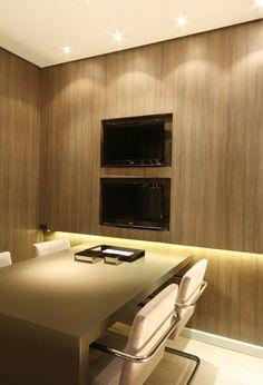 Painel de madeira com nicho. Mesa em laca. Parede revestida em melamínico Teca Palau com iluminação em fita de LED amarela.