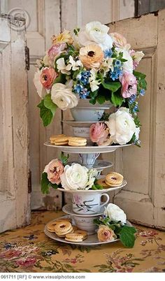 Abundent english garden flowers with teacups and tea pots stacked up high...