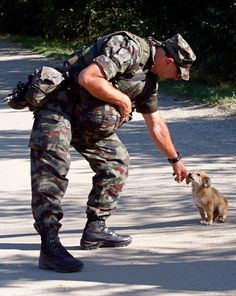 OK, I admit it. Military guys and little creatures steal my heart like THAT *snaps*.  -  A Slovenian soldier pets a puppy on the road in the village of Rudare near Mitrovica