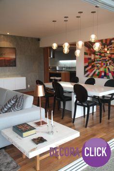 A mesa de laca branca contrasta com as cadeiras pretas e o quadro dá vida ao ambiente.