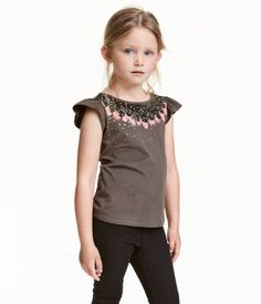 Dark taupe/feathers. Top in soft jersey with a printed design and short, ruffled sleeves.