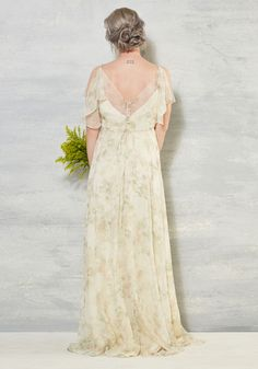 Wayfare through your wedding day with this gorgeous ivory gown by Jenny Yoo leading you in elegance. Whispered with soft mist and pale sage, watercolor-like flowers from its fluttery sleeves and surplice neckline down to its sweeping hem, this buttoned-back, drawstring-cinched beauty takes you on a blissful odyssey into your sweetie's embrace!