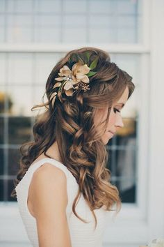 Novia con un peinado decorado con flores y pelo ondulado