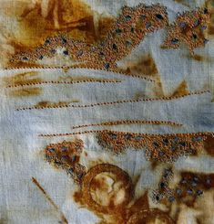Machine stitch on rust dyed and painted fabric.