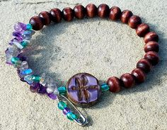 This dragonfly stretch bracelet is 7. Made from dark wood beads, and double strands of stone chips - one strand in amethyst, and the other in a mix of labradorite and iridescent teal glass beads - a purple glass dragonfly charm, and a silver safety pin dangle with purple and teal glass beads. Proceeds benefit EarthJustice:  www.earthjustice.org  Today's environmental challenges are greater than ever. But we live in a country of strong environmental laws—and Earthjustice holds those who break…
