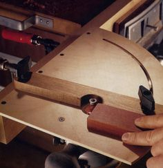 This little router table is perfect to add versatility to a trim router. It's construction is simple. The fence pivots on a carriage bolt and the arc is cut with the same router mounted on a simple trammel.