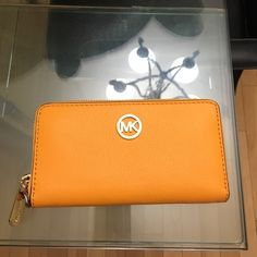 Michael Kors  orange wallet Brand new Michael Kors wallet with out tag never use, nice soft orange leather wallet just right size , 3 credit card slots with 4 compartments,1 zipper goes all around Michael Kors Bags Wallets