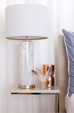 A smooth natural shade tops a glossy, marbled-glass table lamp for a stately, elegant design accent.