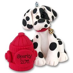"""Meet Sparky the Dalmatian!  Sparky is a darling little Dalmatian and one of Deb's """"Puppy Pal Collection"""". He is hard to resist with his big eyes and floppy ears! Sparky is special in that he has his own little fire hydrant. This puppy Christmas ornament may be easily personalized with a name on the fire hydrant. Handmade from polymer clay and designed by Debi Allison. He is packaged in his own little clear acrylic box with his dog house in the background."""